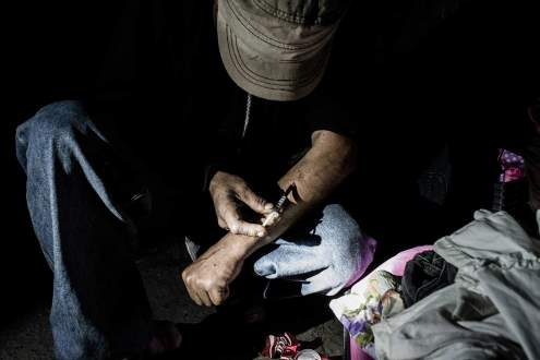 A drug addicted injects heroine in the tunnel of El Bordo , Tijuana
