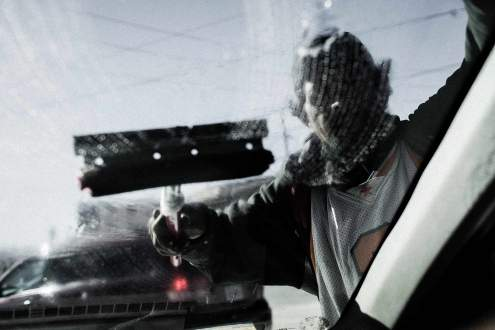 A migrant is washing car windshields in the street of Tijuana