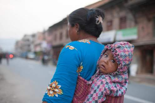 A woman carries her baby on her back in a street of Bhaktapur