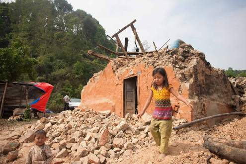 a child plays in front of her destroyed house, Nepal