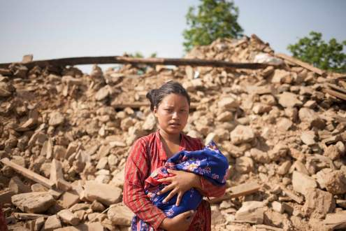 A woman in front of her destroyed house, Nepal