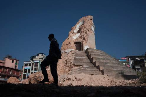 Policeman patrols the destroyed Dharahara tower in Kathmandu, Nepal