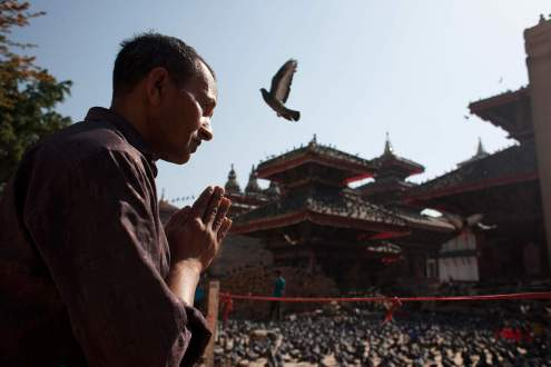 A man prays in front of a destroyed temple in Kathmandu