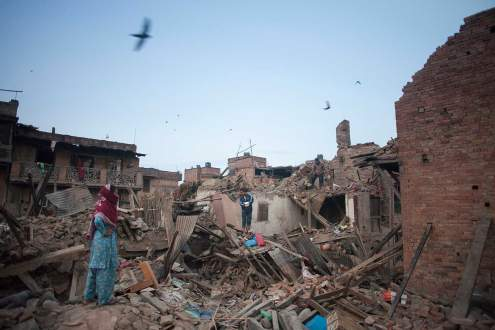 People stand on collapsed houses, outskirt of Kathmandu