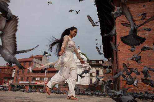 A Nepali young woman plays with pigeons at Pashupatinath Temple