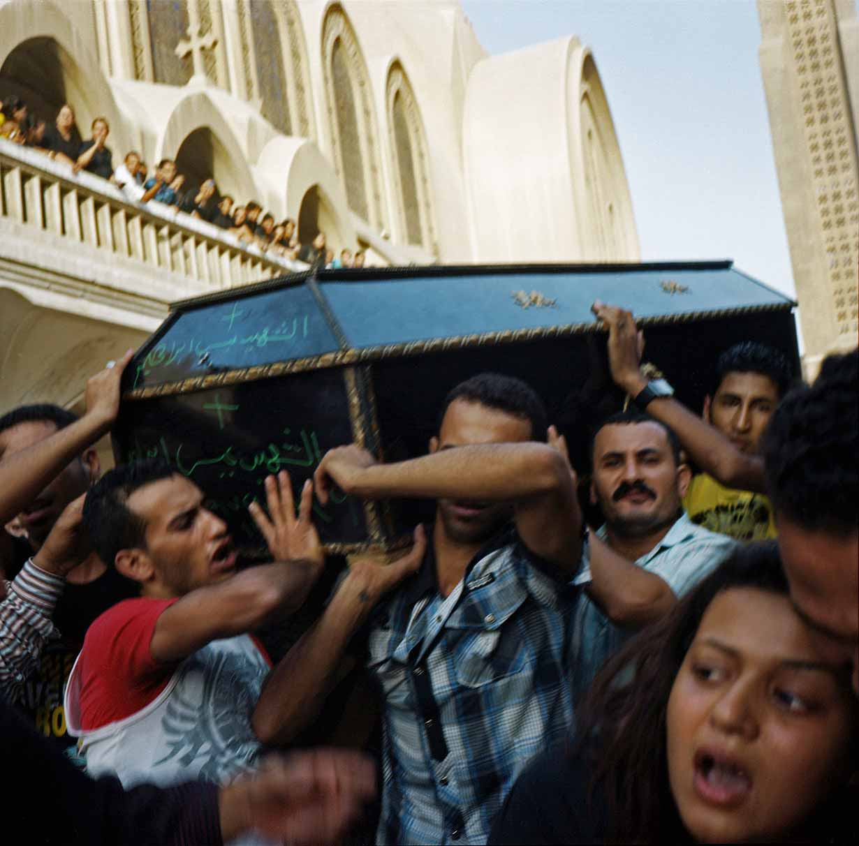 Relatives of coptic victims carrying coffins out of the Abasseya Churc
