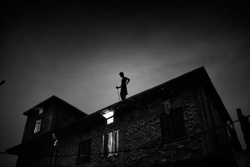 man on the roof of a factory Hazaribagh tannery area Dhaka, Bangladesh.