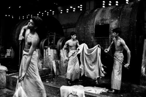 Bangladeshi workers process leather