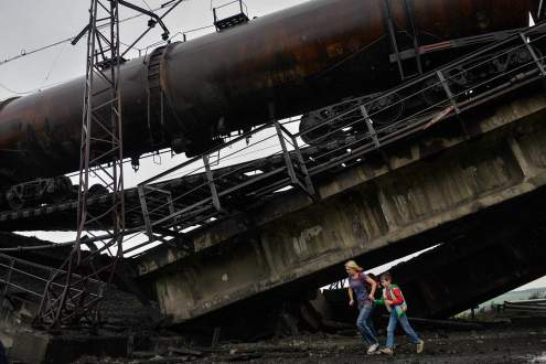 Civilians escape through the railroad bridge blown up by Donetsk People Republic partisans.