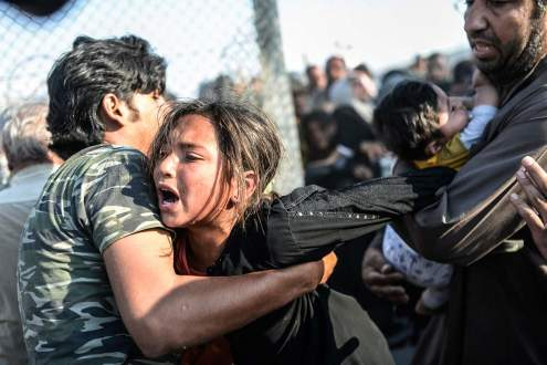 A refugee man holds a crying girl at Turkey border