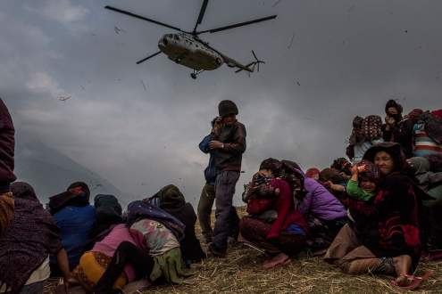 Nepalese villages watch a helicopter picking up a medical team