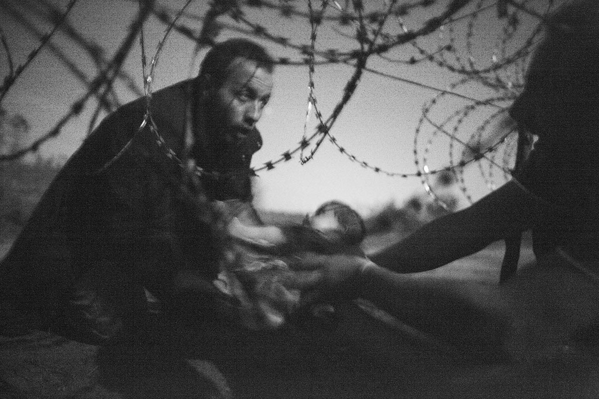 Warren Richardson, Hope for a New Life. A man passes a baby through the fence