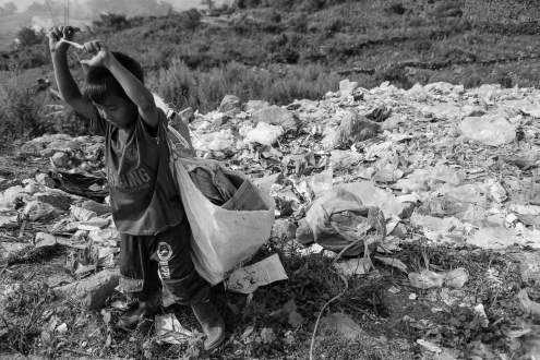 A boy collects paper trash