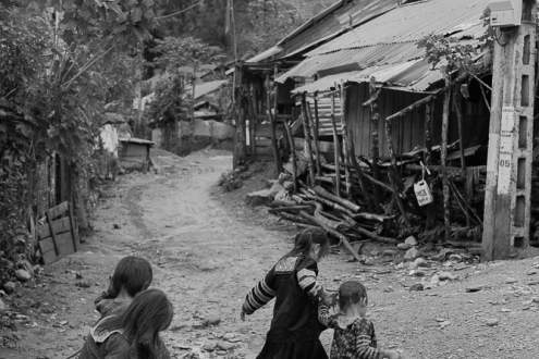 A group of girls is walking through a mudded street in their village