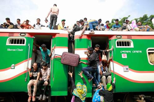 Bangladeshi people try to climb on the roof of a train