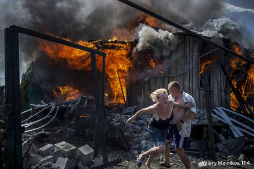 Civilians escape from a fire at a house destroyed by an air attack in the Luhanskaya