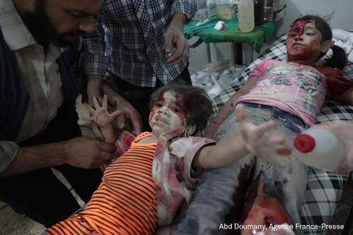 A Syrian girl cries out as a wounded child lies next to her