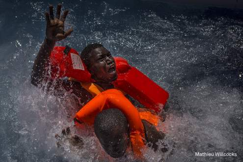 Mediterranean Migration - Two men panic and struggle in the water during their rescue