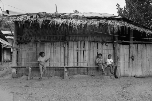A group of Mabri are sitting in front of an house