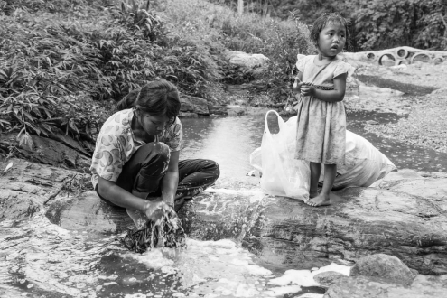 A girl, is washing clothes on a creek
