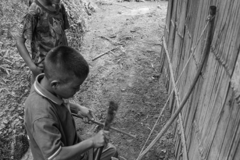 A Mlabri boy is making a toy bow and arrows