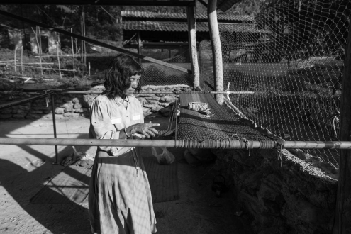 A woman is weaving hammocks