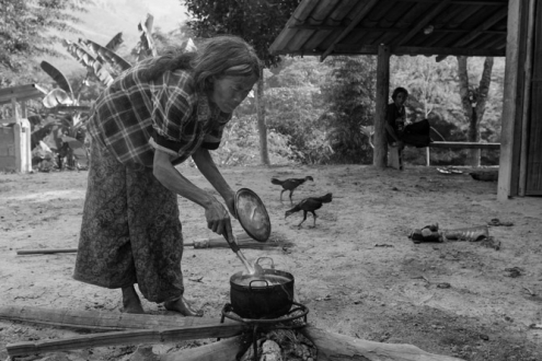 A woman is cooking food in front of her house