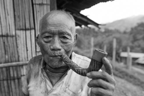 Portrait of Pa smoking a bamboo pipe