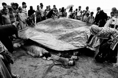 Bangladeshi villagers cover bodies of Rohingya women