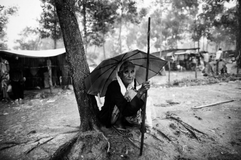 Rohingya Muslim woman sits in the rain