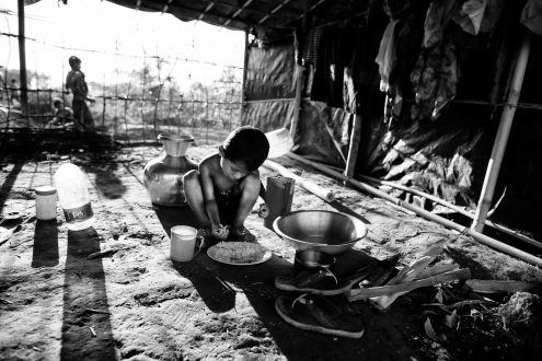 Rohingya child takes his lunch at a refugee camp